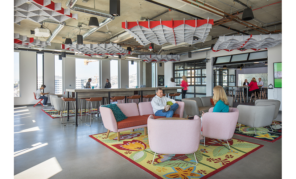 "Stand-up meeting bars, pops of color, and informal seating characterize the many collaborative meeting spaces; the light-filled main ""promenade"" of the office; and a fun garage door connects the cafe-lounge with the design studio."